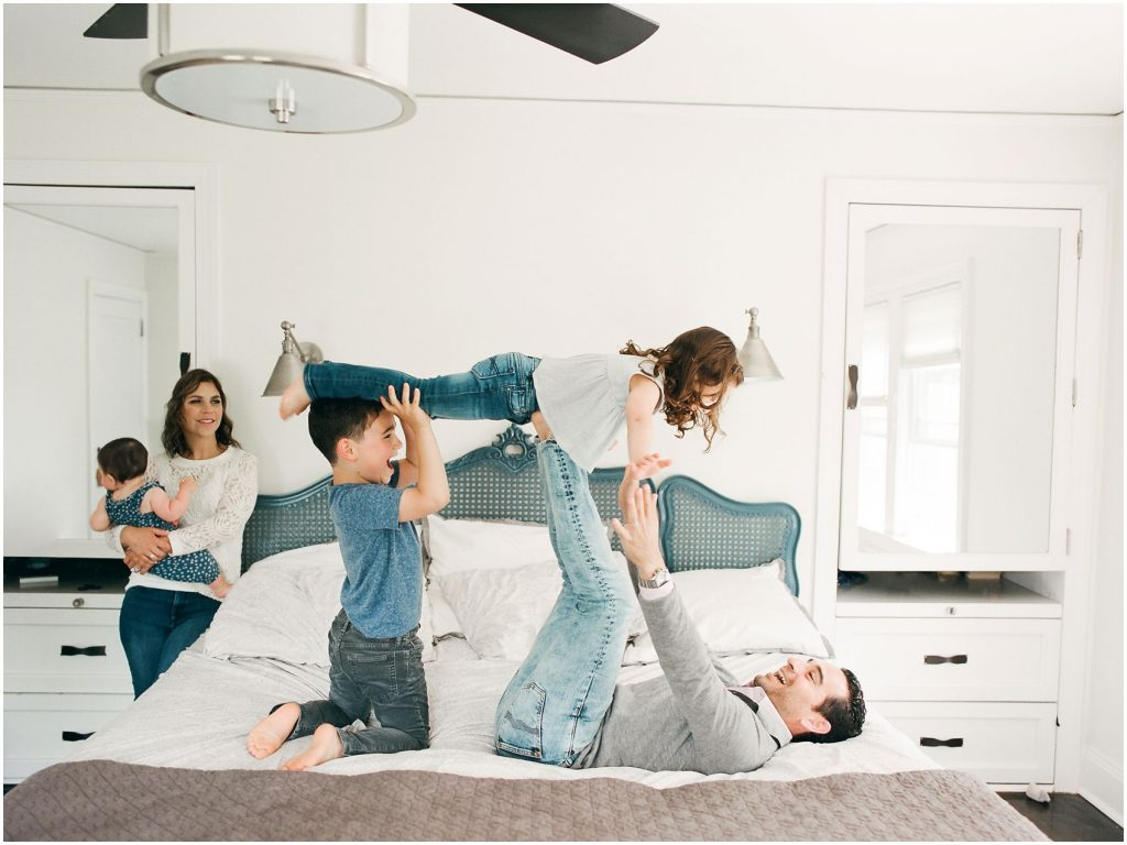Father is playing airplane on bed with two kids while smiling mom looks on in family session in Montclair NJ