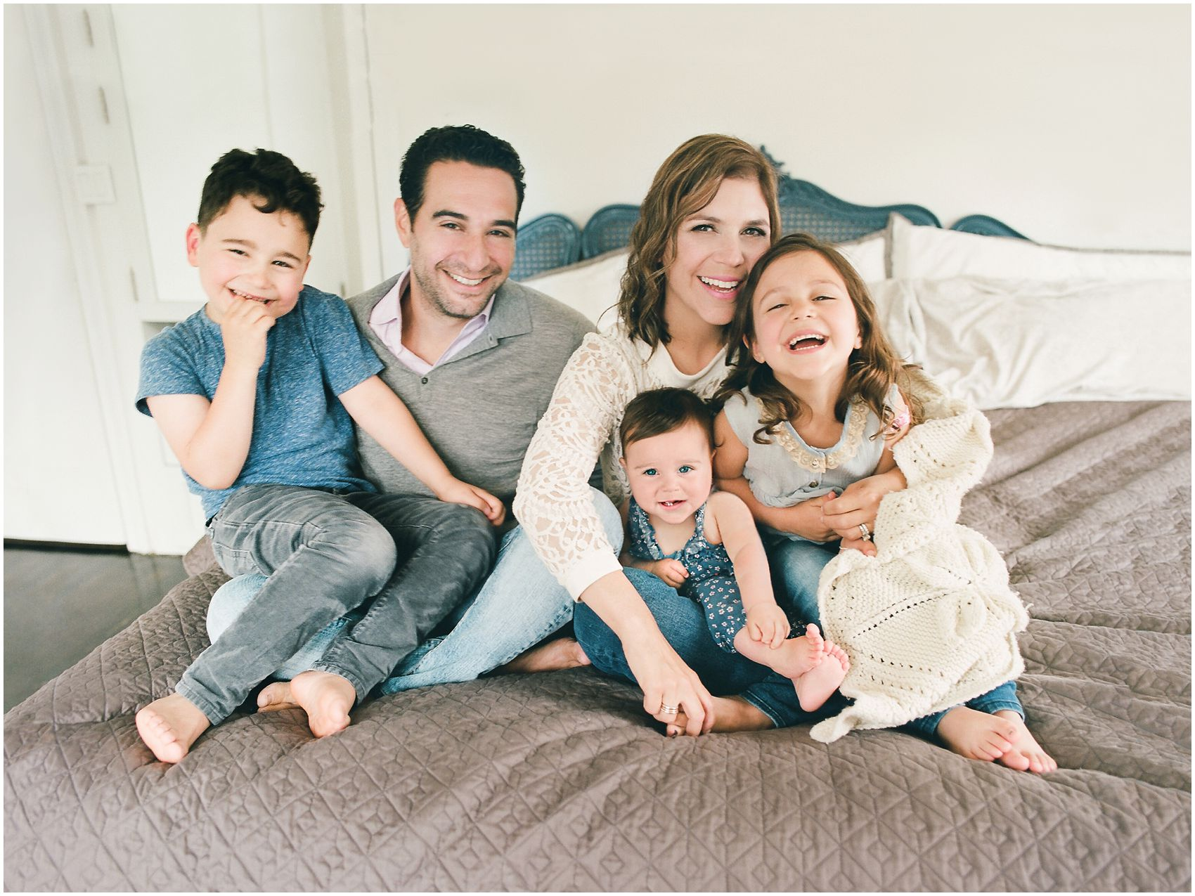 family of parents and 3 kids is all snuggled up on bed for the lifestyle family photography at home