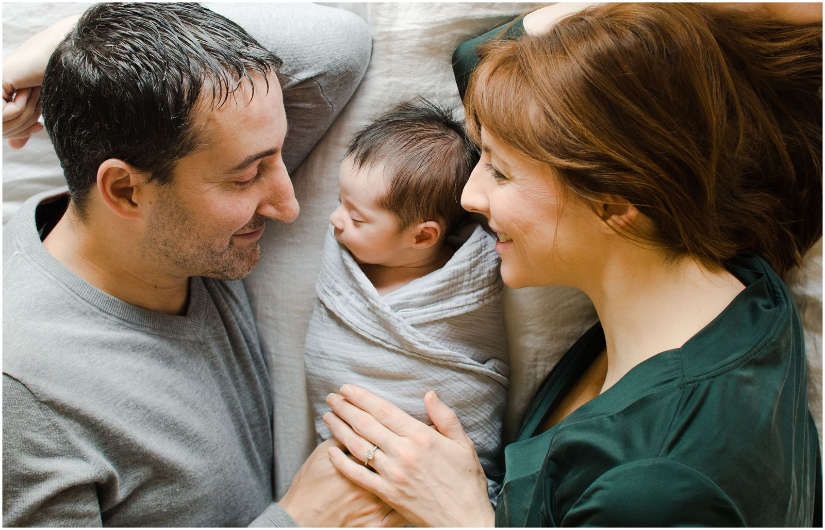 smiling mom and dad lying down with their new baby girl during the best newborn photos session