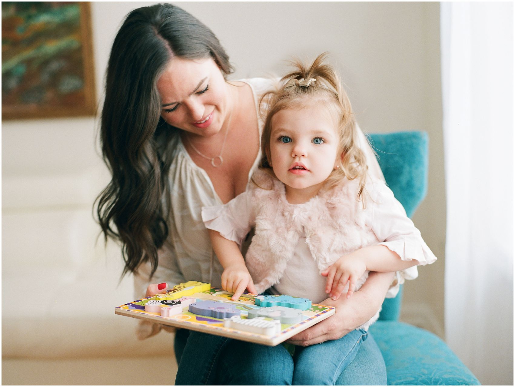 blonde little girl with blue eyes playing puzzles with mommy