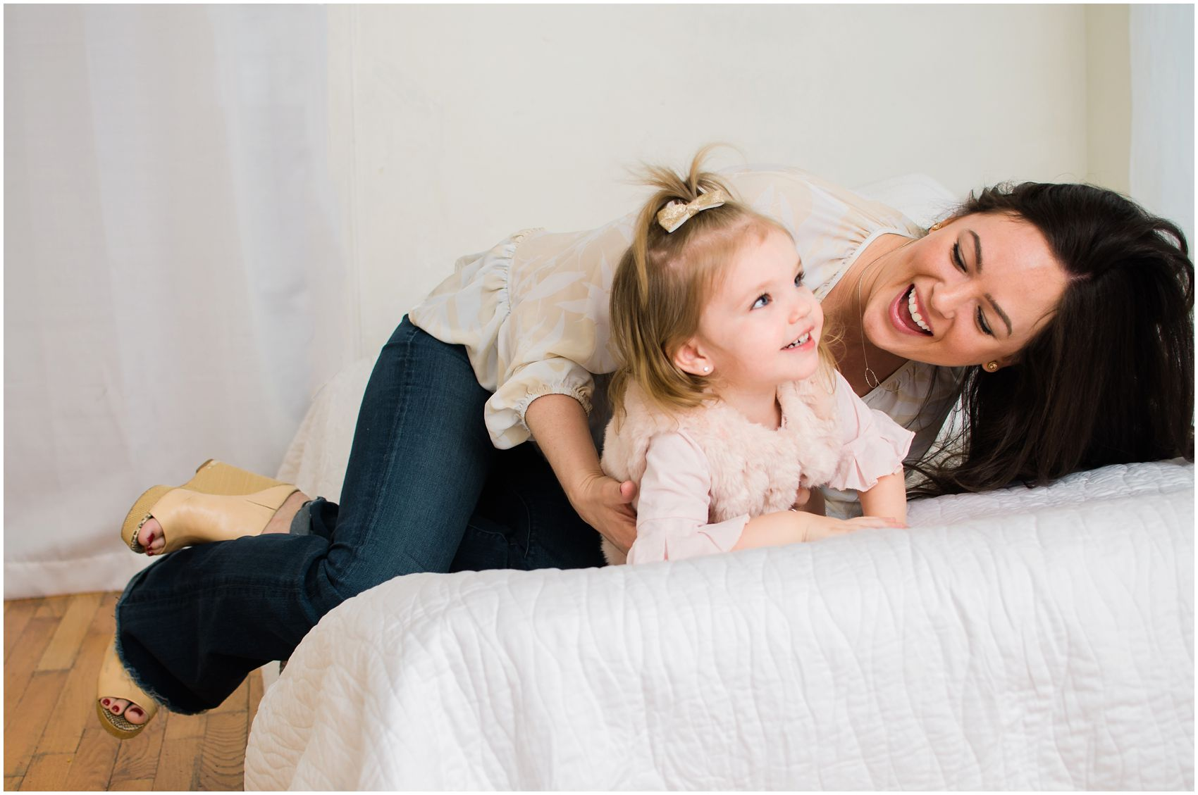 mom and little girl having fun on bed