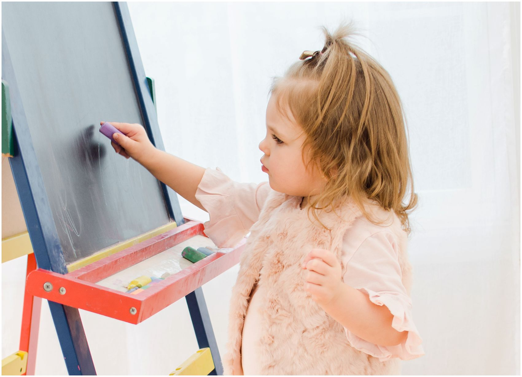 little girl with a ponytail drawing on the easel board
