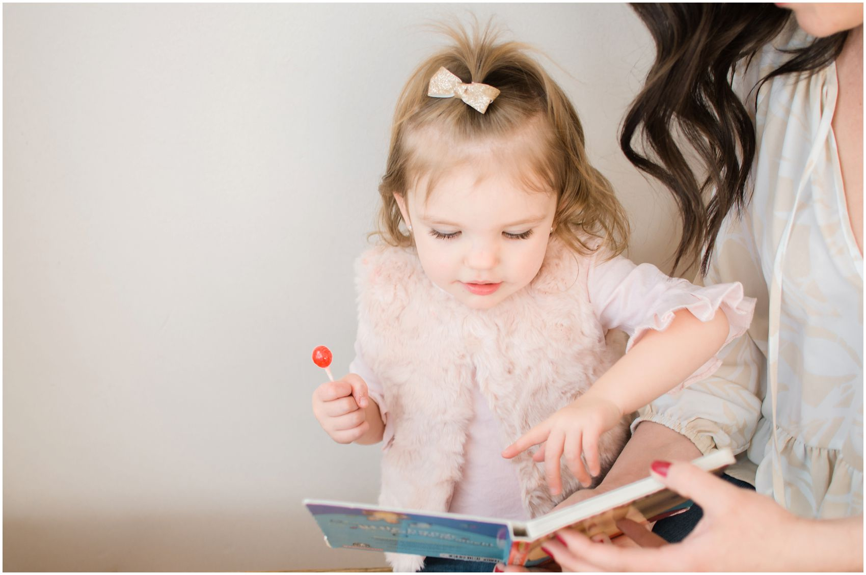 little girl eating a red candy and reading a book with her mom in family photography NYC