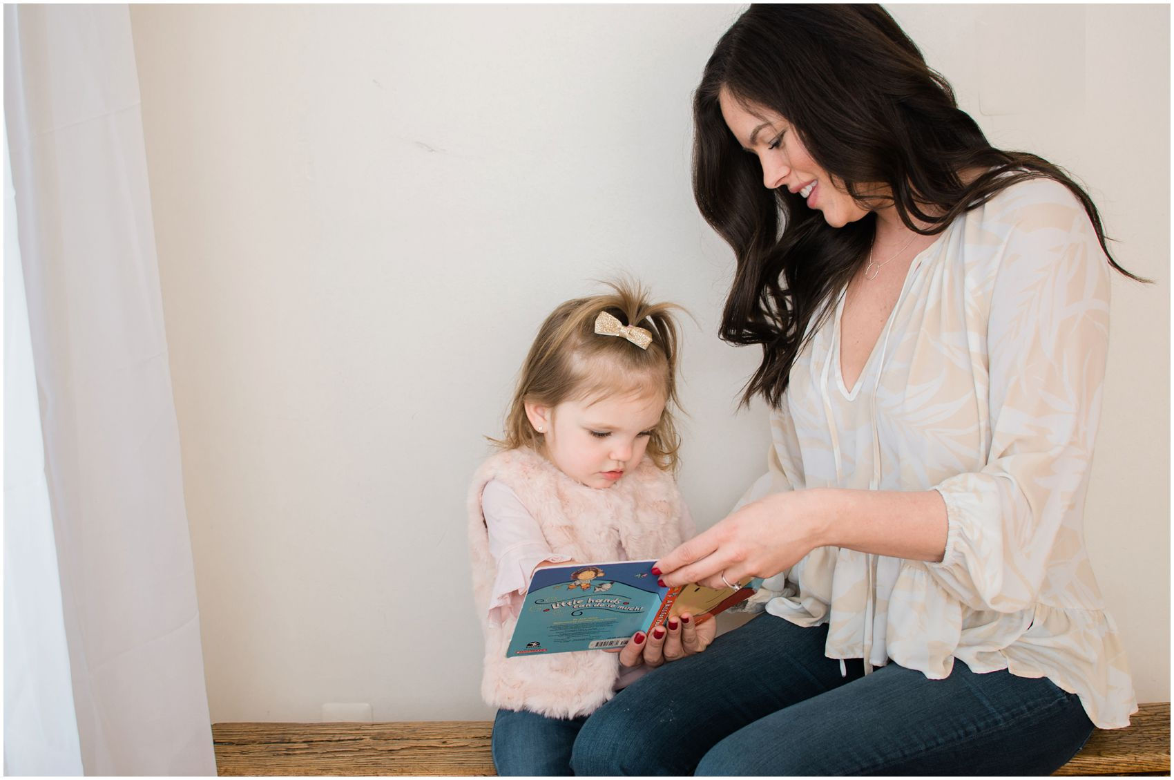 mom and her 2 year old daughter reading a book