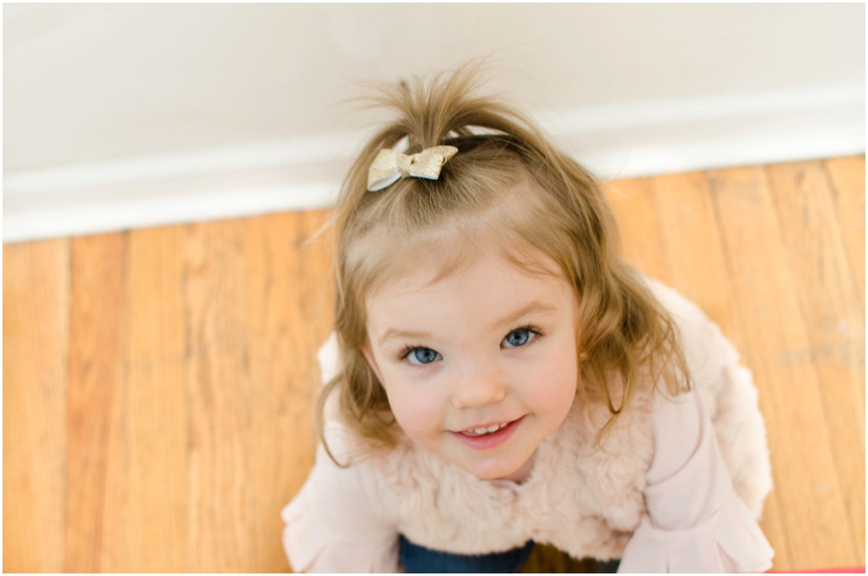 little blonde girl with blue eyes looking up and smiling