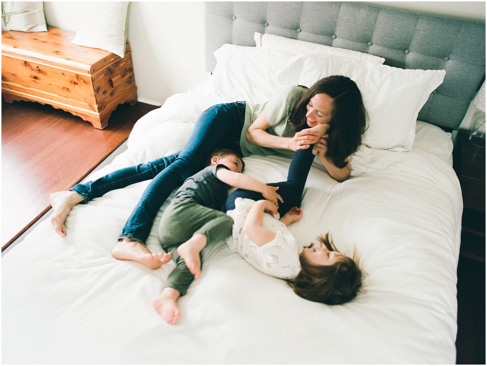 kids are cuddling in bed with mom during a home family session in NYC