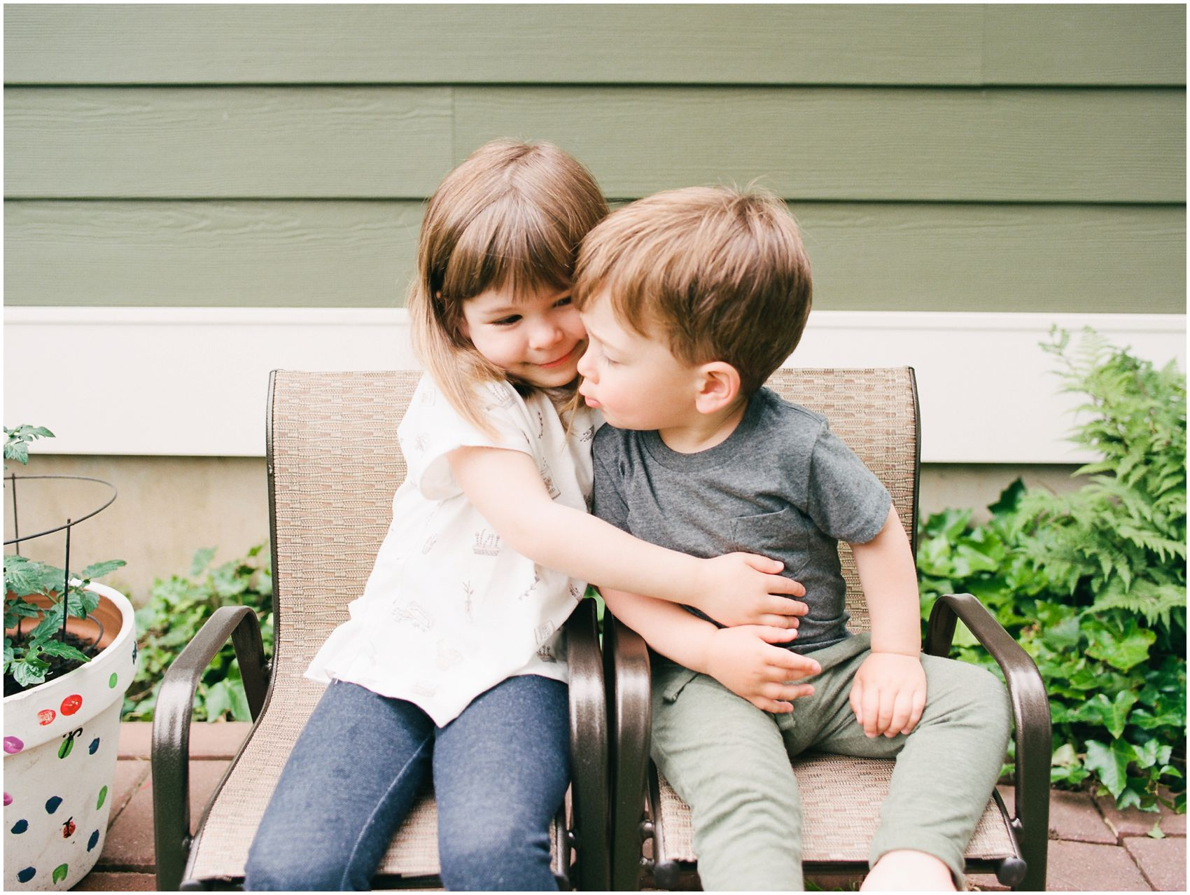 little girl hugging her brother in the backyard garden in NYC home family session