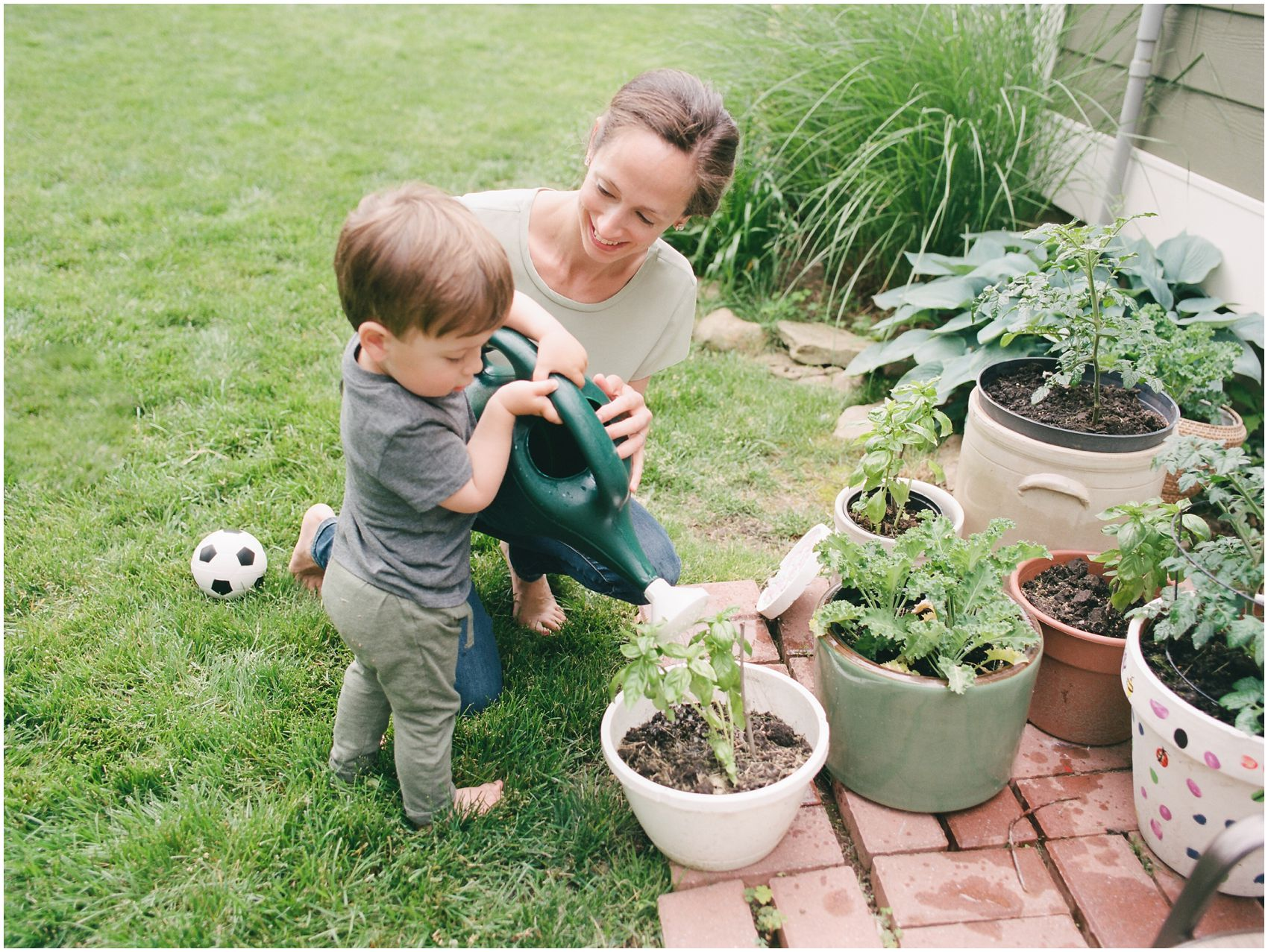 little boy is gardening with his mom in their backyard