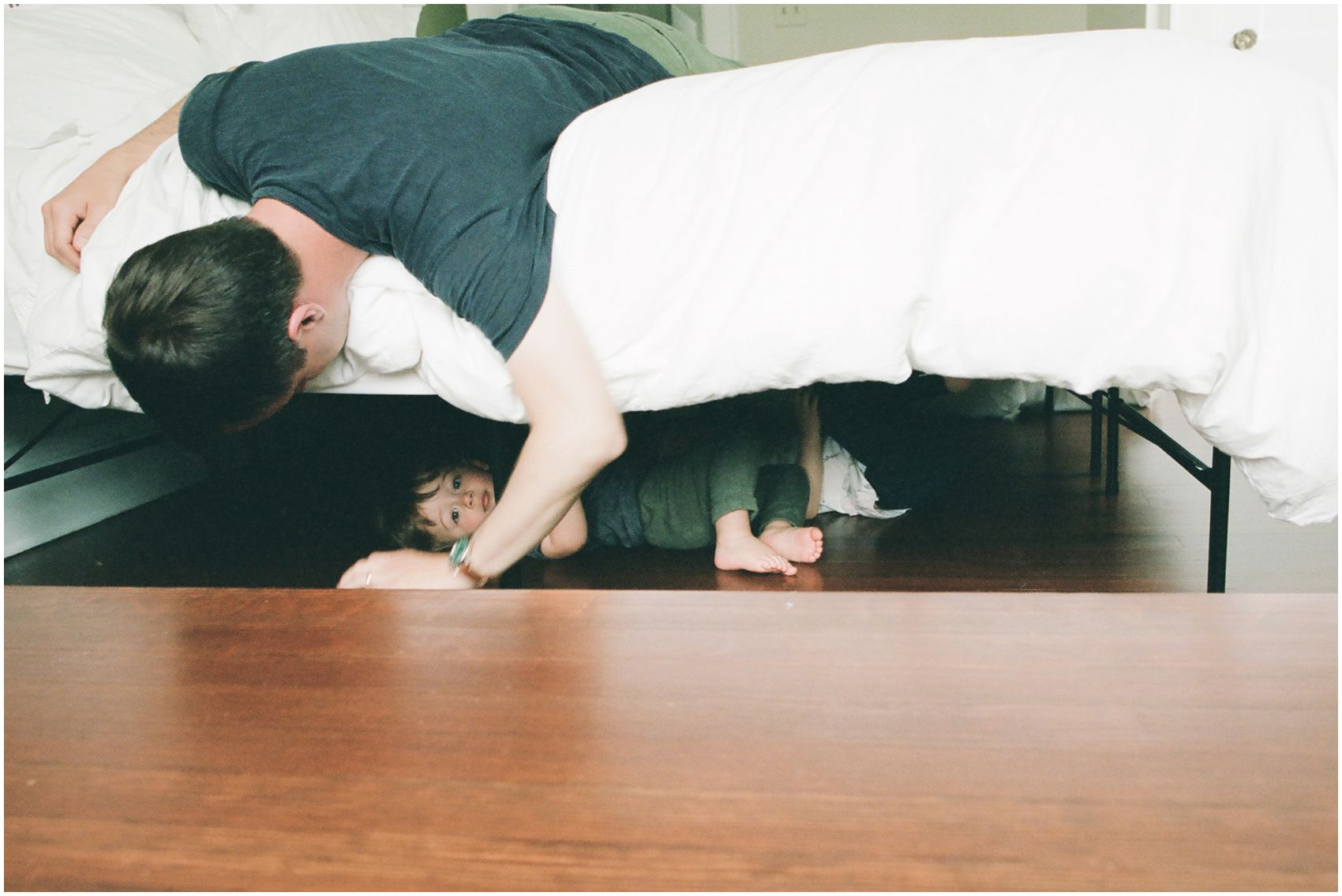 dad is peeking at his little son hiding under the bed
