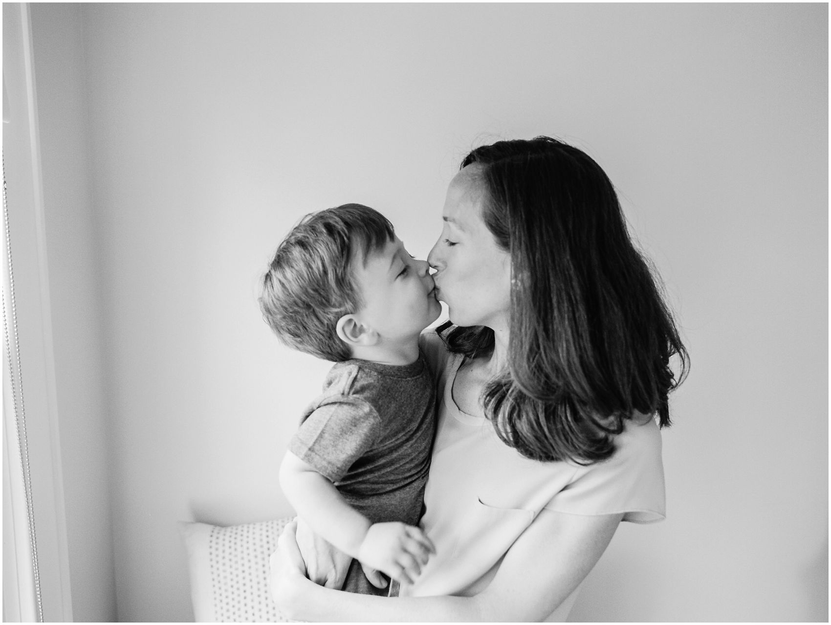 mama is kissing her little boy at NYC home family session