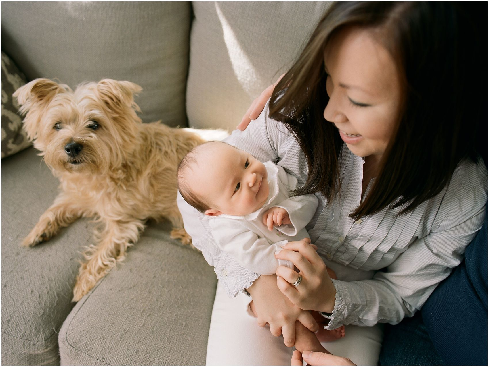 mom smiling and sitting with a baby and a family dog in NYC newborn photography session