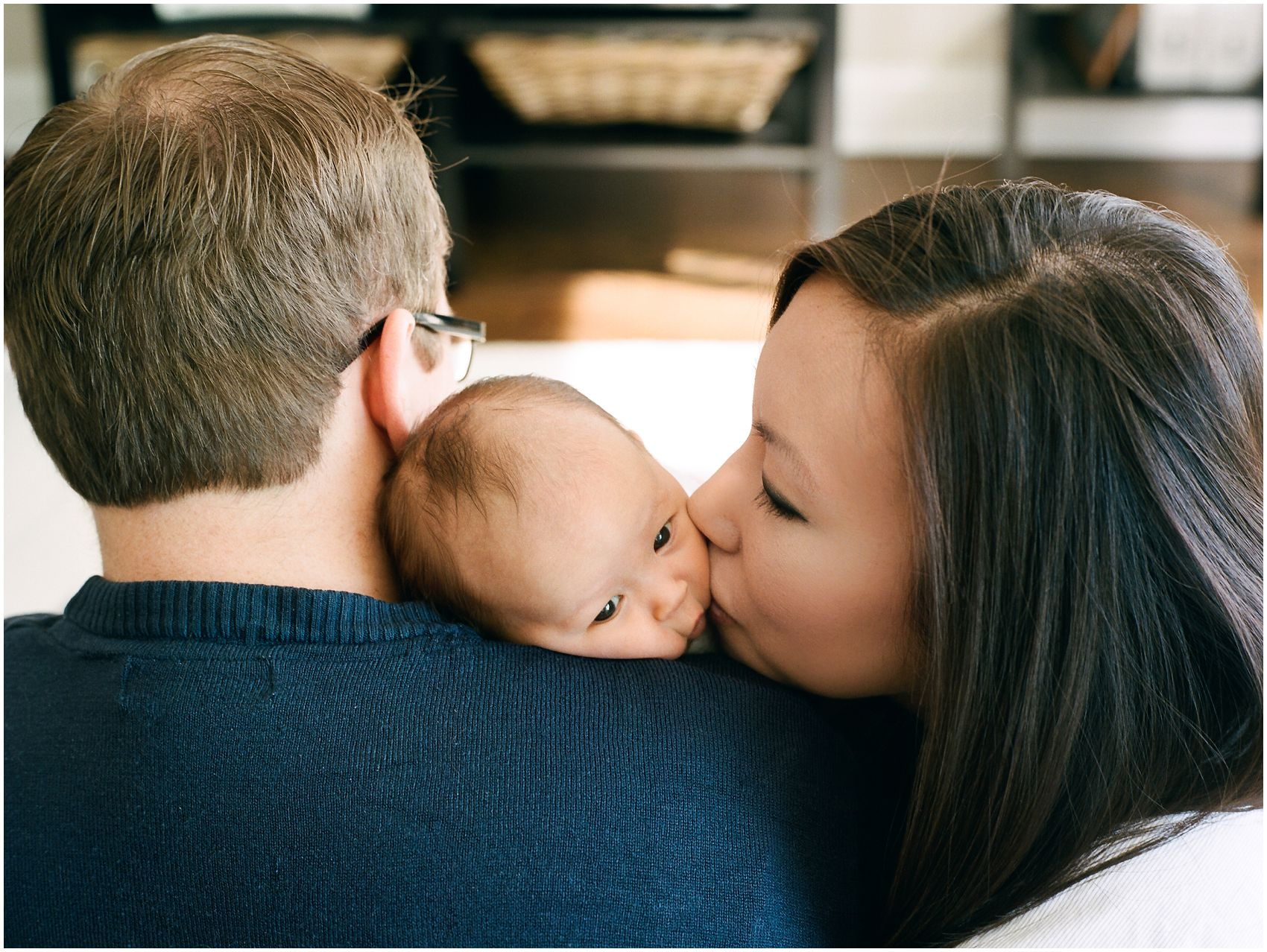 mom and dad kiss and squish their baby cheeks in a newborn portrait