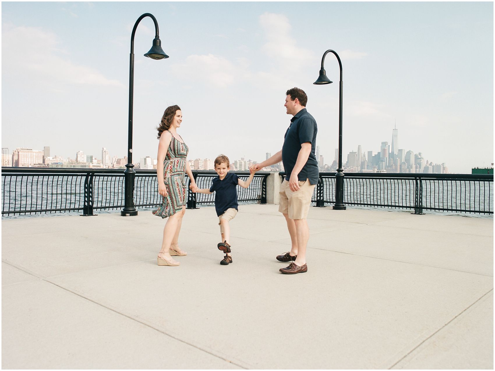 Family Photography NYC with mo, dad and son having fun by Hoboken Waterfront