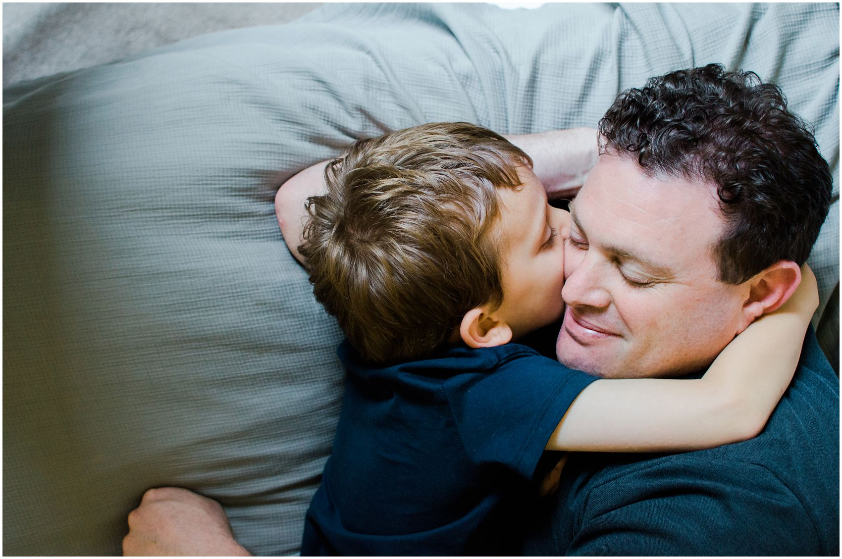 son snuggling with his dad and giving a hug during a fame family session at Hoboken NJ home