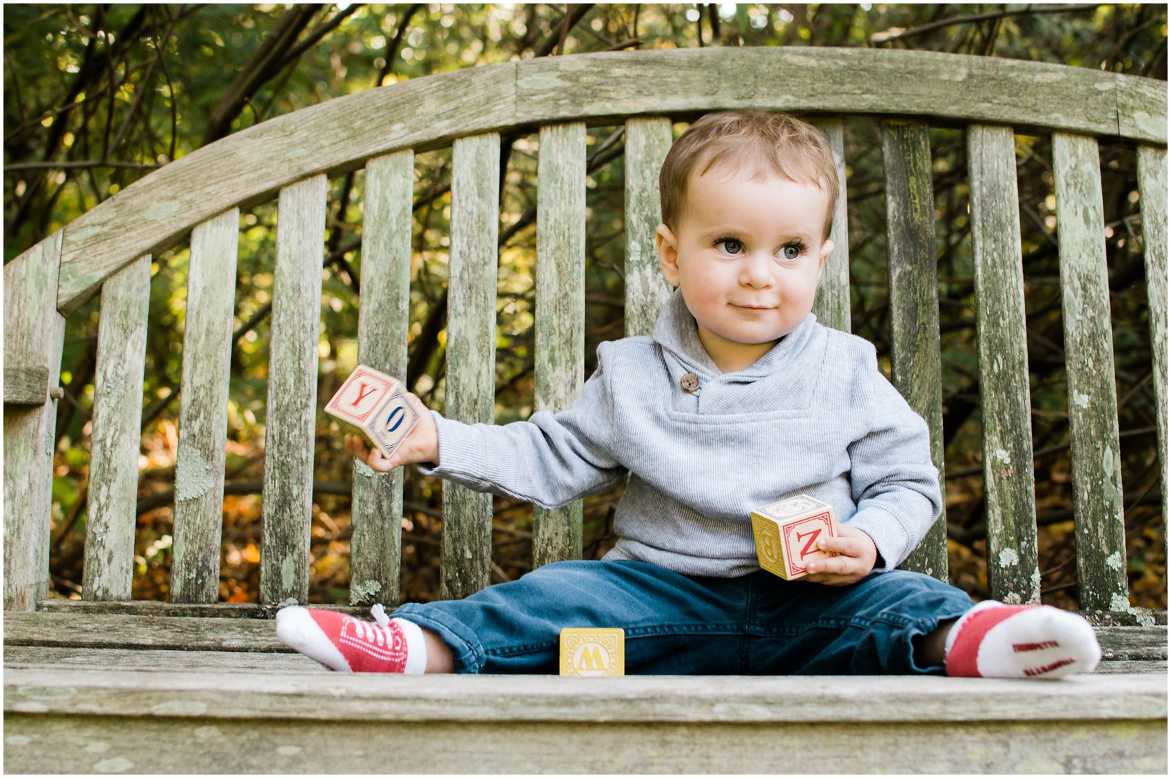 little baby wearing blue and grey clothing sitting on bench playing with abc blocks