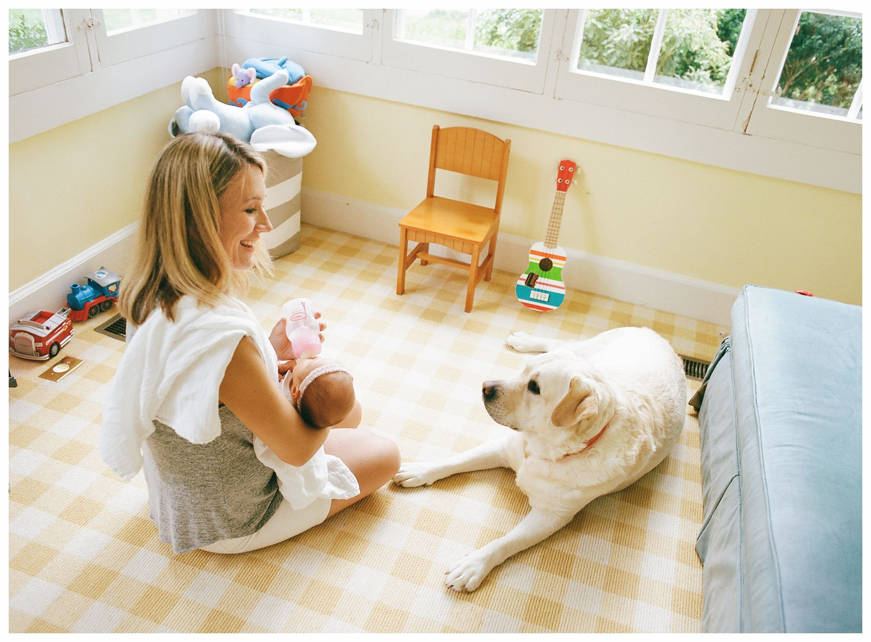 happy mom feeding the baby on the yellow carpet in the sun room with the family dog looking at her in Summit NJ