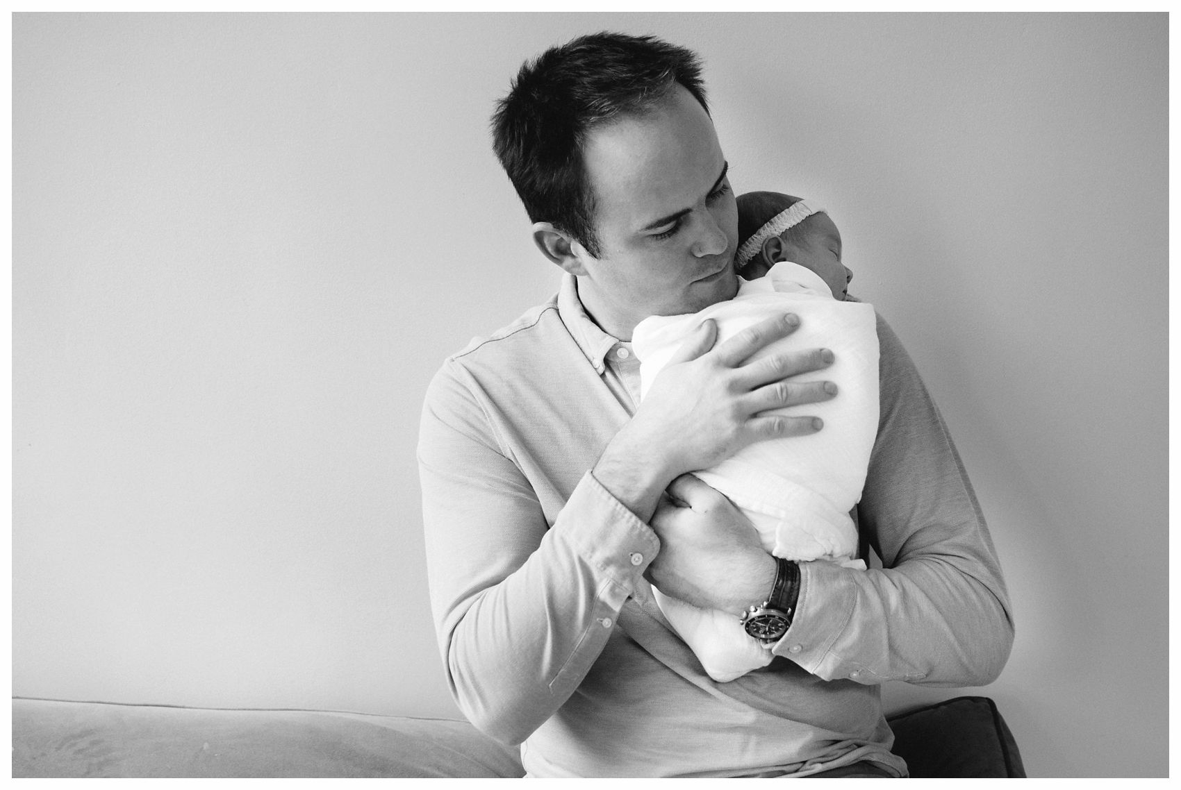 an emotive newborn portrait in NYC of a young father snuggling with his baby girl