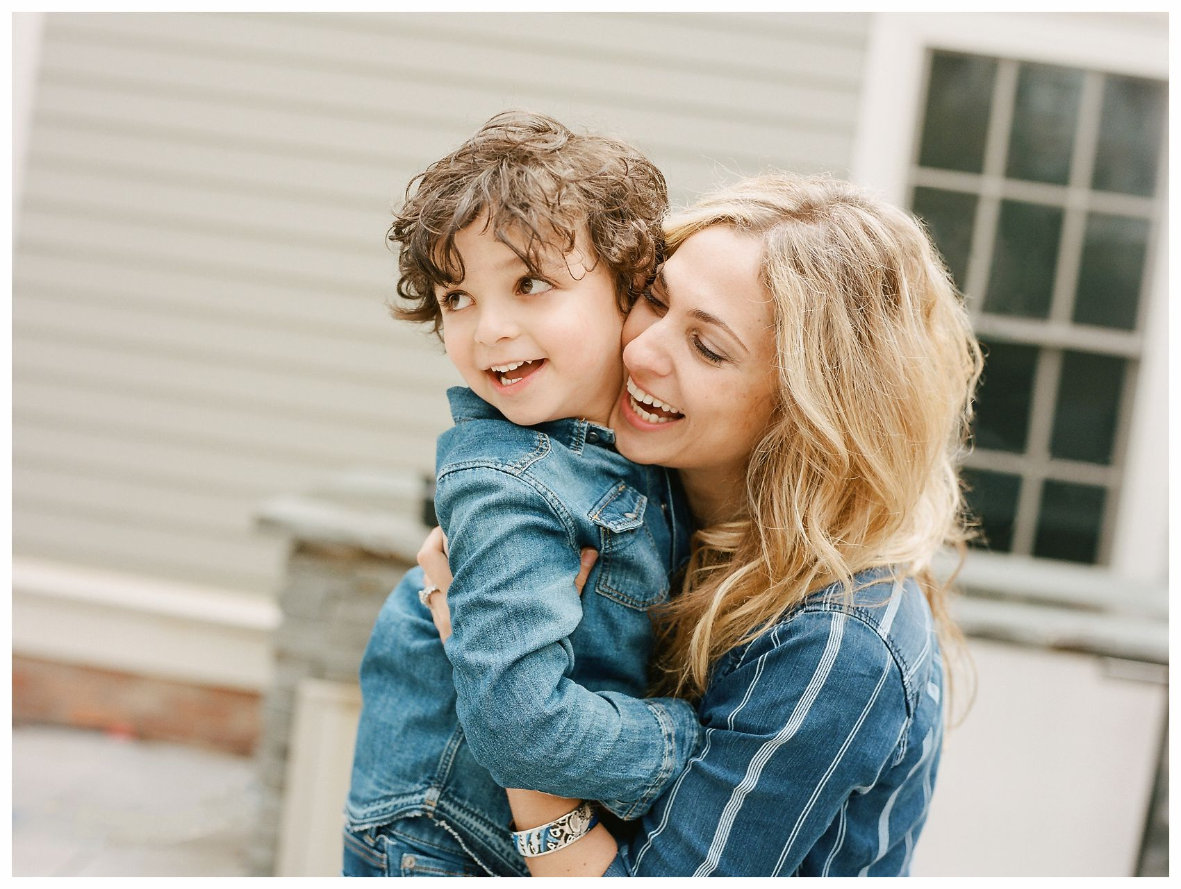 blond mom with beach wavy hair hugging and laughing with her son in a family photo in Montclair NJ