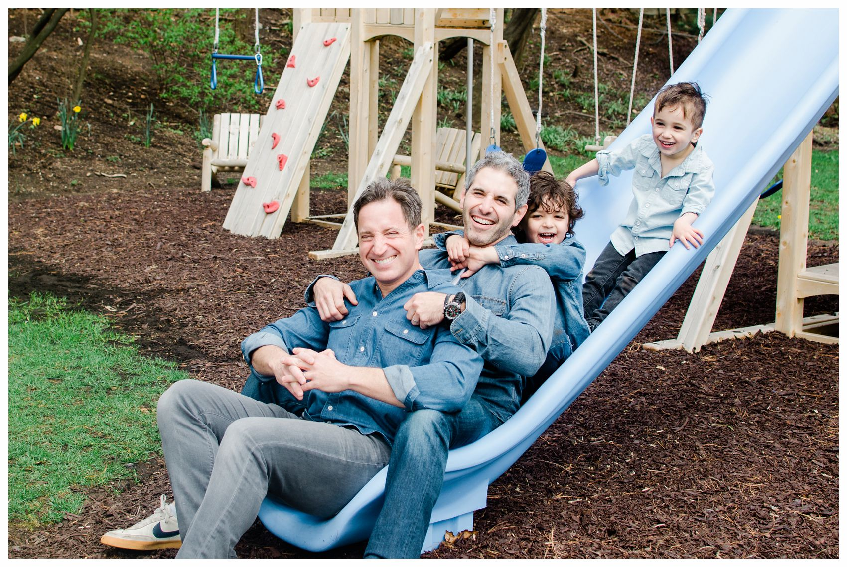 laughing fathers and sons are sliding down the blue slide at their family photos in Montclair NJ