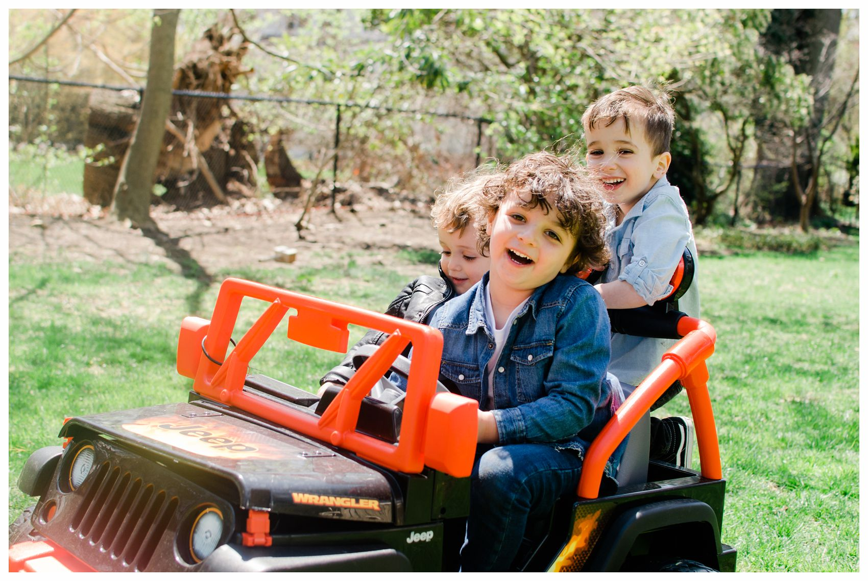 three laughing kids riding a car in their backyard in New Jersey
