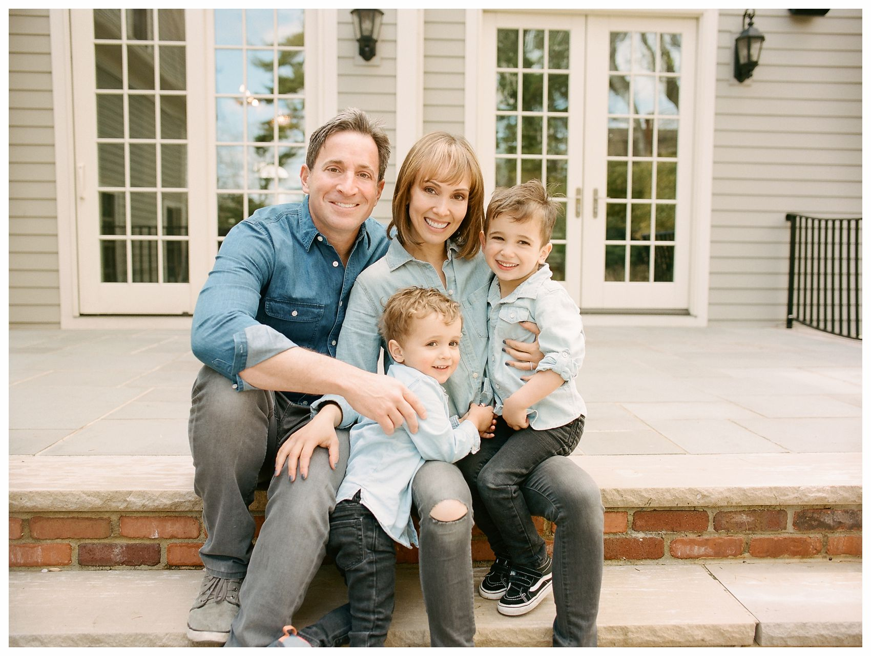 family photography of a family of 4 with two little boys sitting on their porch wearing denim jeans in Essex County