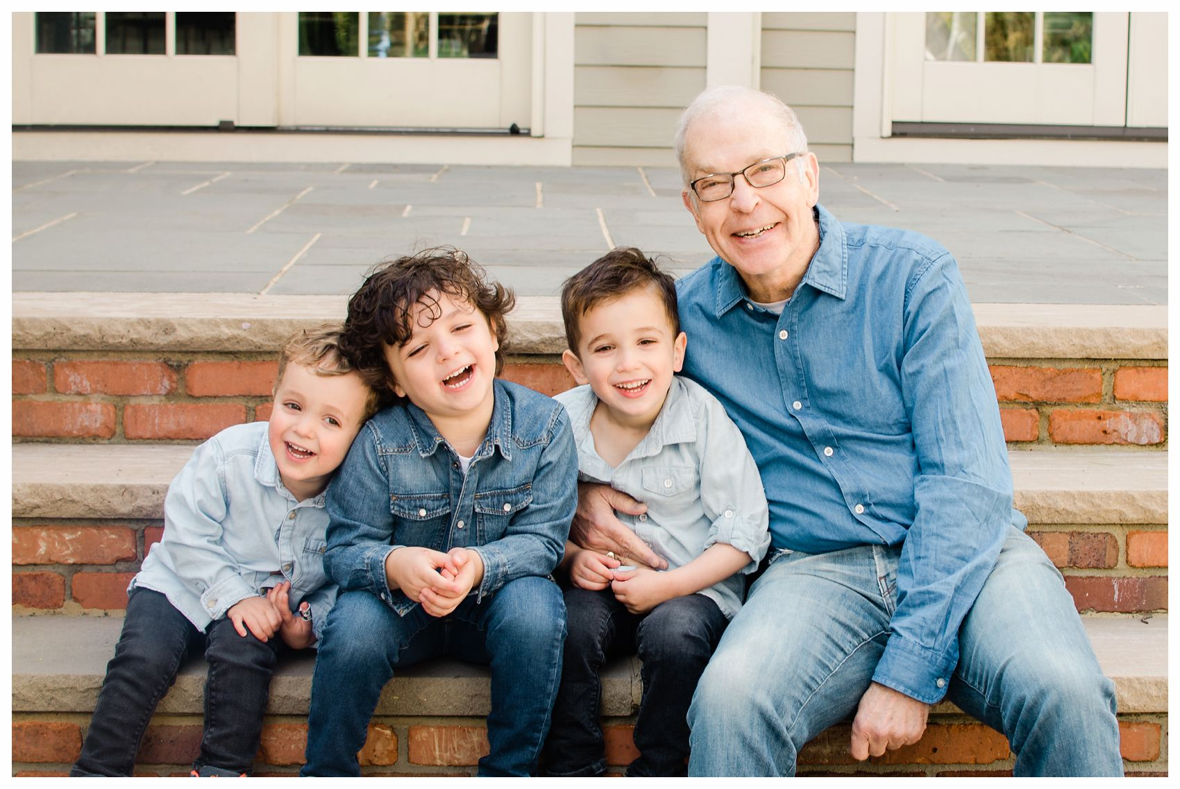 grandfather is laughing and giggling with grandsons on the steps of their home in Montclair NJ for an extended family portrait