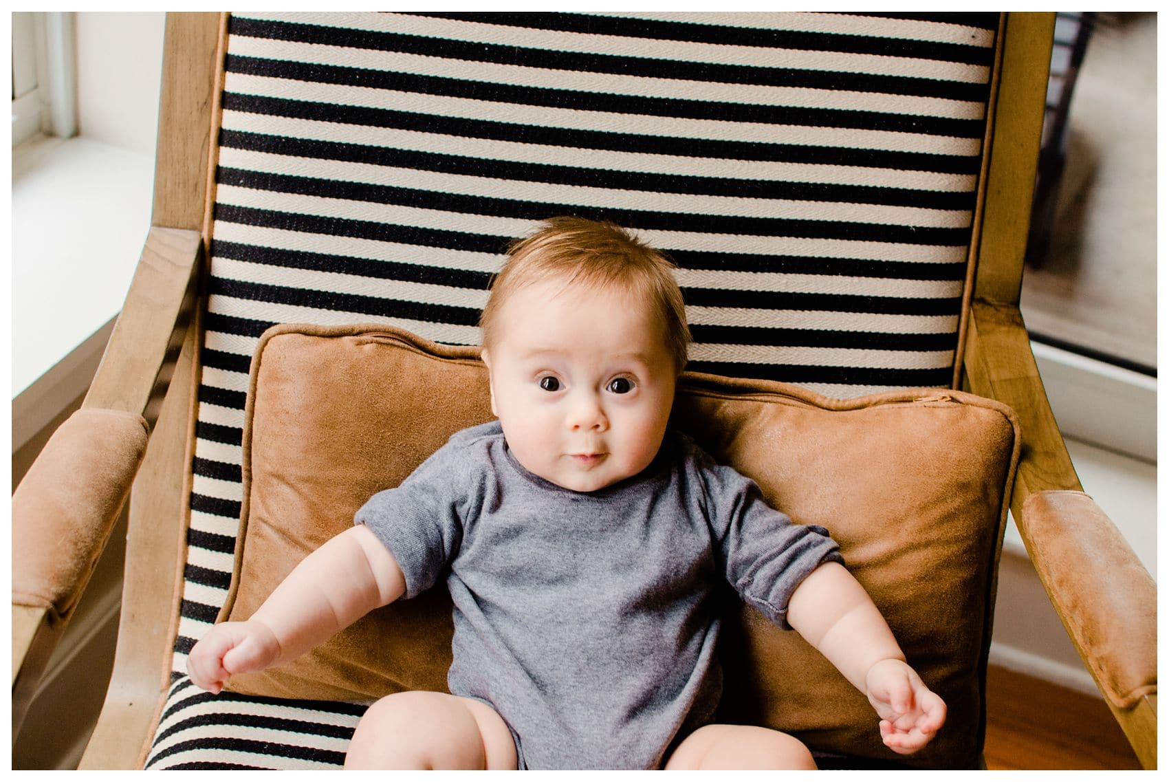 5 months old cute baby boy sitting on the chair and has a funny expressions in Hoboken