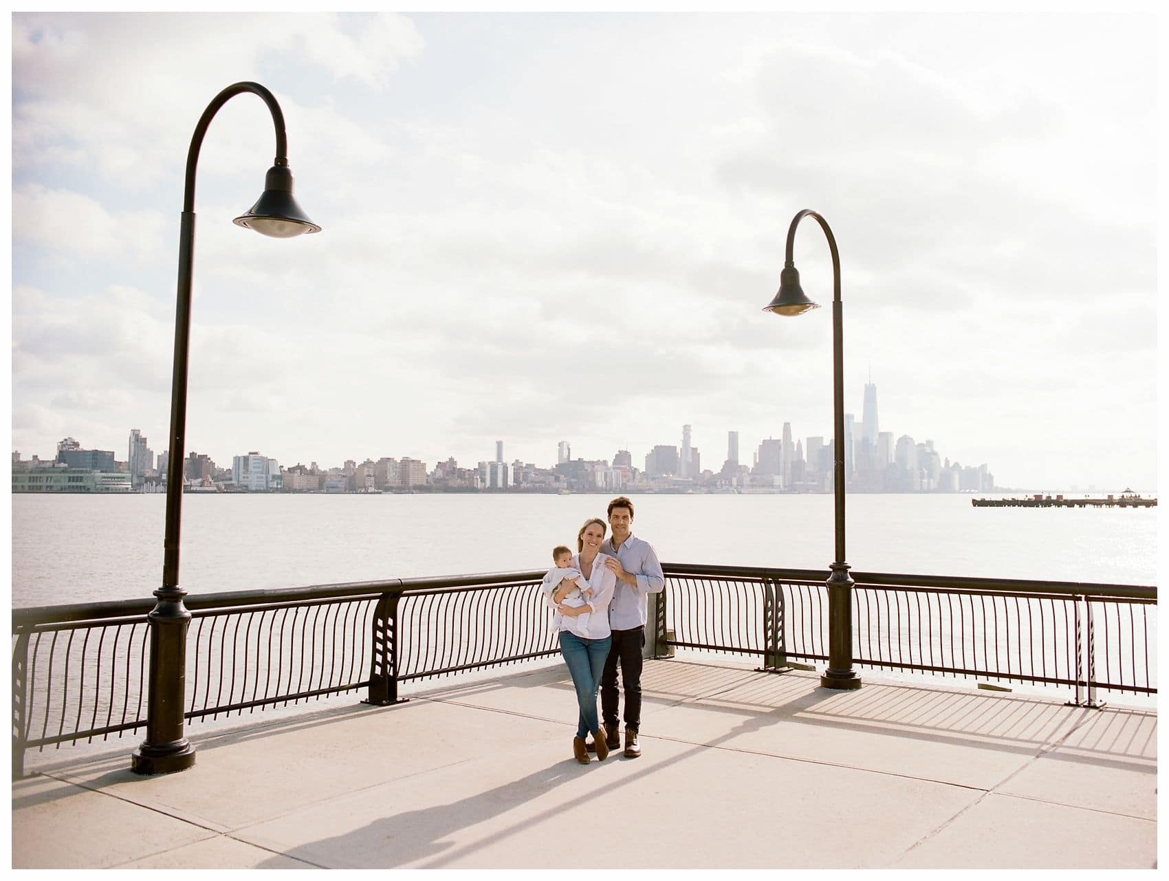 parents and the baby stand by NYC skyline at the Hoboken Waterfront