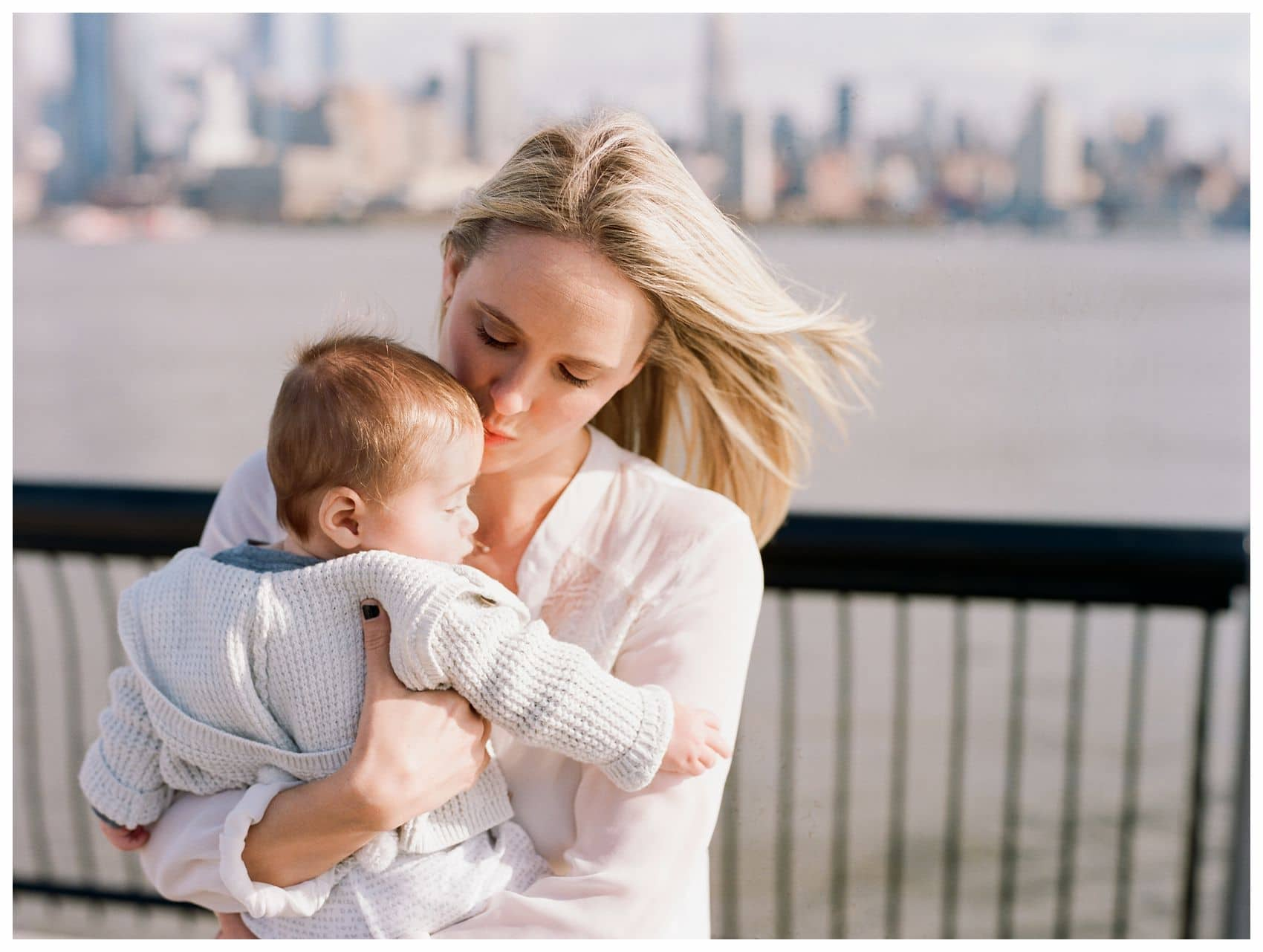 mom kissing her baby boy by Hoboken waterfront behind NYC Skyline