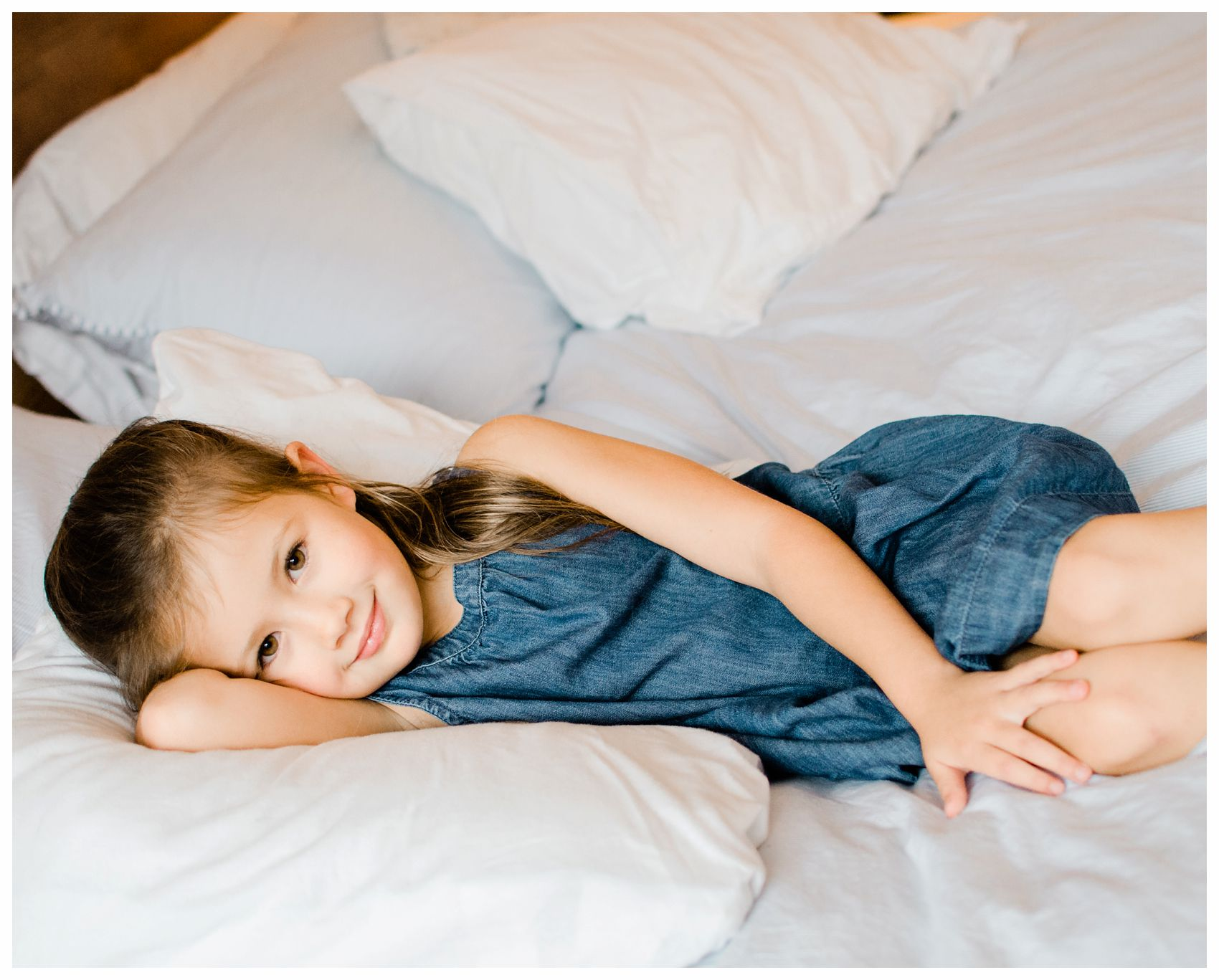 a little girl in denim laying in bed for family photos in NYC