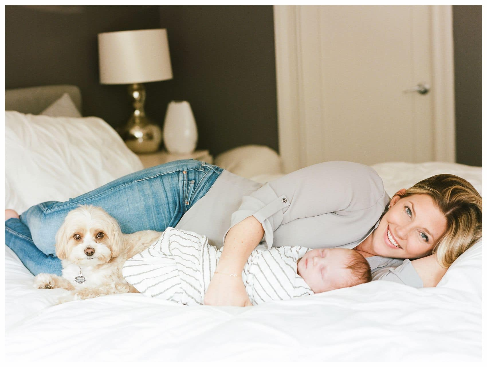 Miriam Dubinsky shares on how to choose the best newborn photographer with lifestyle photo of mom snuggling with baby boy and family dog on bed