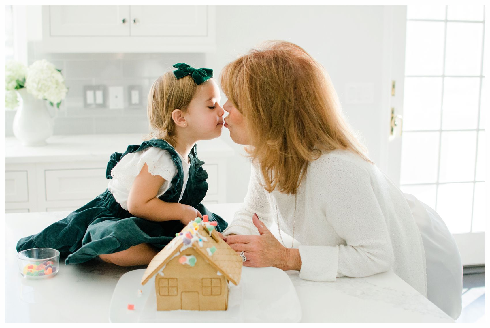little girl kissing her grandmother in the kitchen next to gingerbread house in Essex County NJ