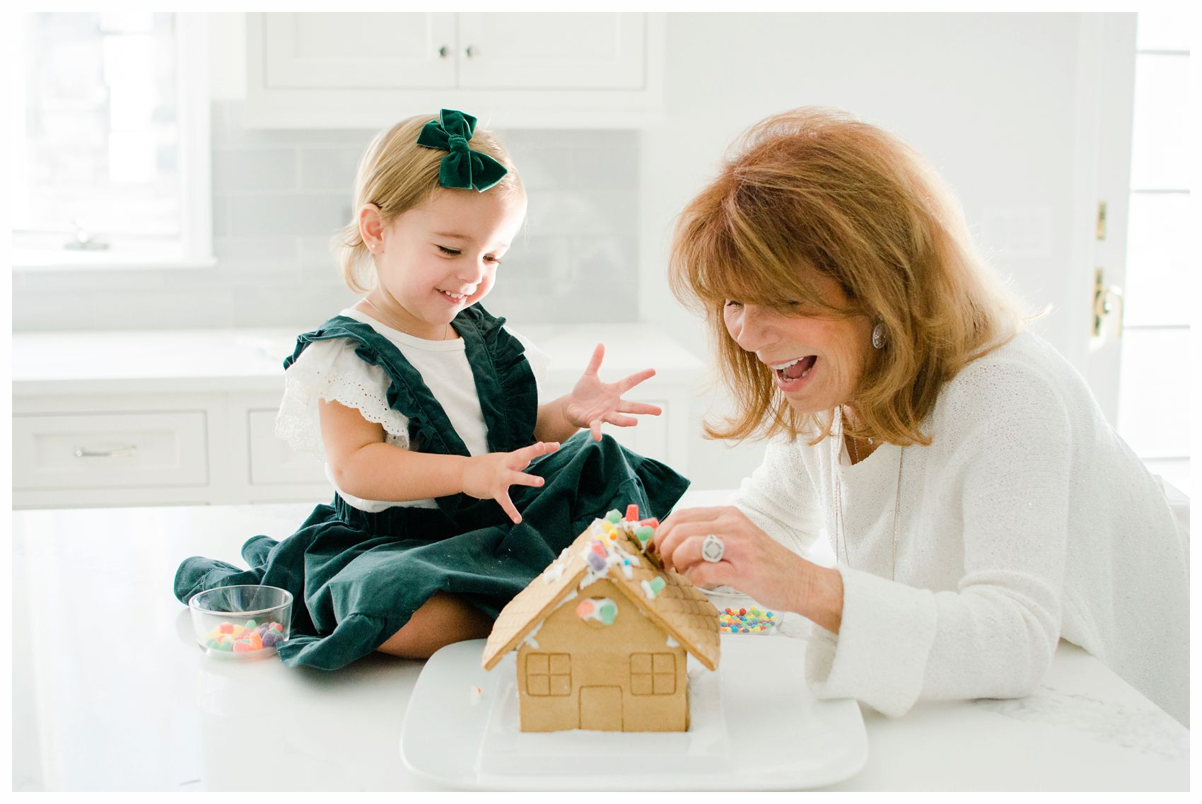little girl building a gingerbread house with her grandmother for the holiday