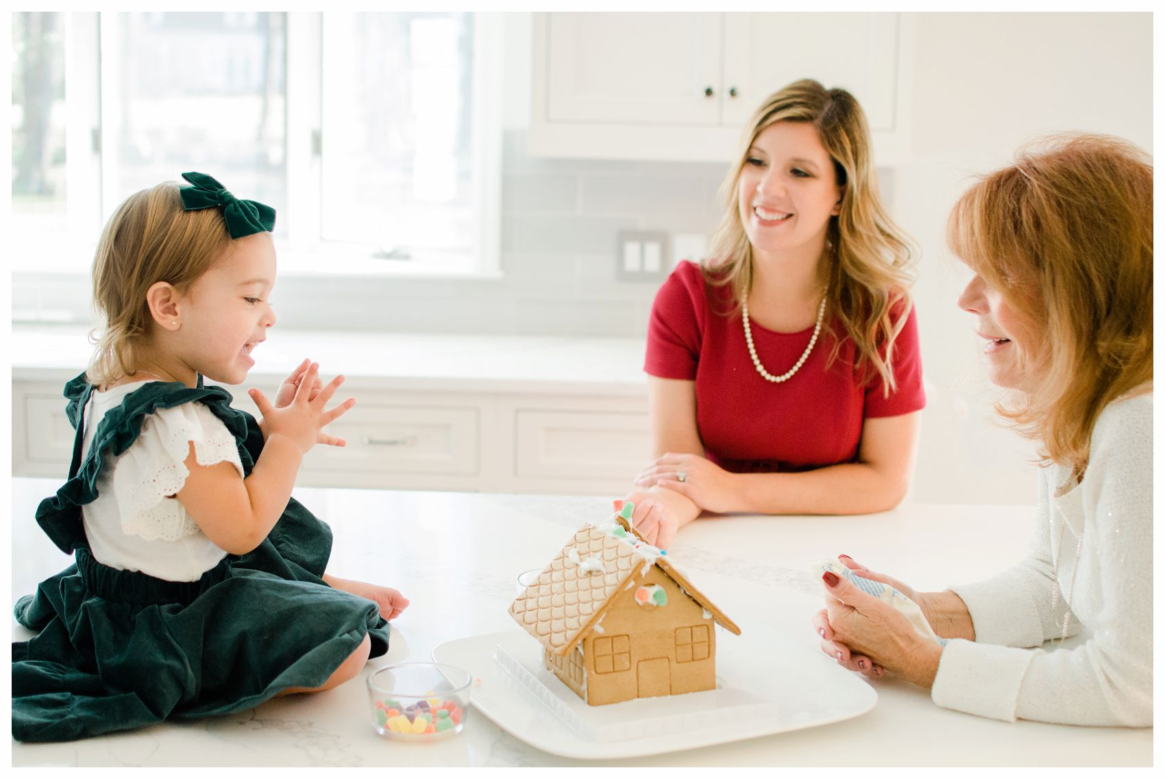 mom daughter and granddaughter building a gingerbread house