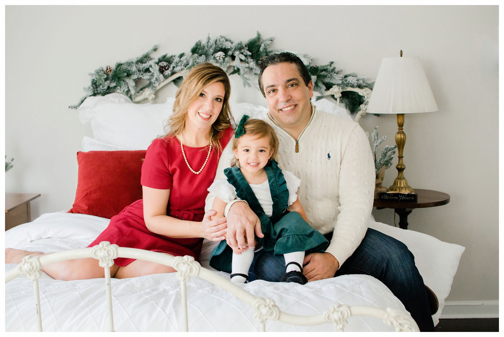 family holiday photo shoot at NJ home on the bed with mom dad and little girl