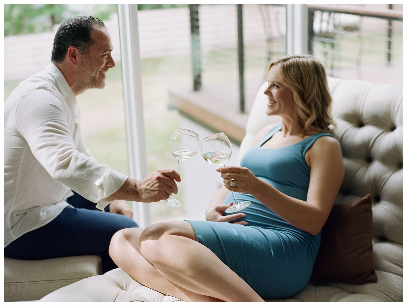 maternity session at home with a champaine toast on the couch of their New Jersey home